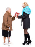 Grandaughter giving gift to her grandmother. Granddaughter giving gift to her grandmother on a white background stock photography