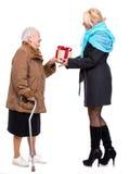Grandaughter som ger gåvan till hennes farmor Arkivbild