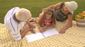 Grandchild drawing with grandparents outdoors. Kid is drawing with colorful pencil. Childs development of art skills stock video