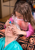 Grandchild dripping eye drops to grandmother Stock Photography