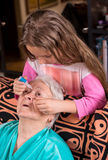 Grandchild dripping eye drops to grandmother Royalty Free Stock Photography