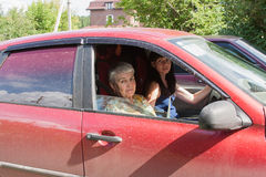 A grandchild drove a grandmother on a car. By a canicular sunny day stock image