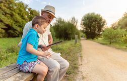 Grandchild and grandfather using a tablet outdoors Royalty Free Stock Photography