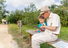 Grandchild and grandfather using a tablet outdoors Stock Photography