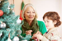 Grandchild and grandmother decorating christmas tree Stock Photo