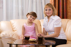 Grandchild and grandmother drink tea. Grandchild and grandmother sitting on a sofa and drink tea Royalty Free Stock Images