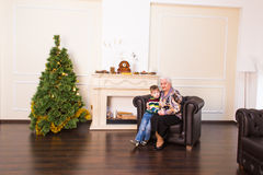 Grandchild and grandmother near the christmas tree Stock Photos