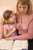 Grandchild and grandmother read book Stock Photos