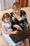 Grandchild and grandmother and use laptop Royalty Free Stock Images
