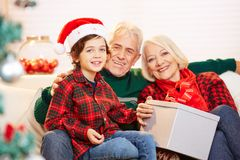 Grandchild and grandparents celebrating christmas stock images