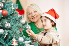 Grandchild helping grandmother to decorate christmas tree royalty free stock photos