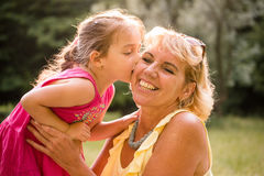 Grandchild kisses grandmother in nature Royalty Free Stock Photography