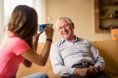Grandchild photographing grandfather on her phone Royalty Free Stock Images