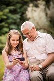Grandchild shows grandfather smartphone Stock Photography