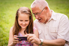 Grandchild shows grandfather smartphone. Senior men with his grandchild looking together on photos in smartphone - outdoor in nature stock photo