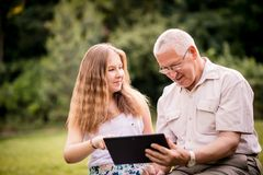 Grandchild shows grandfather tablet. Senior men with his grandchild looking together on photos in smartphone - outdoor in nature royalty free stock images