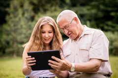 Grandchild shows grandfather tablet Stock Photography