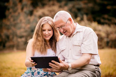 Grandchild shows grandfather tablet Royalty Free Stock Photo