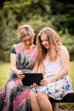 Grandchild shows grandmother tablet Stock Images