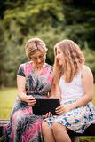 Grandchild shows grandmother tablet Royalty Free Stock Photo