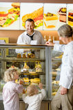 Grandchildren asking grandmother for cakes at cafe Stock Images
