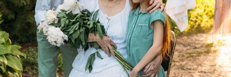 Grandchildren, children hugging grandmother, elderly woman. meeting grandmother and grandchildren. grandmother embraces grandchild. Ren, brother and sister stock photos