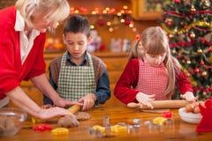 Grandchildren and  grandmother baking Christmas cookies Stock Images