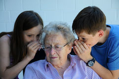 Grandchildren and grandmother. Young and old, grandchildren share a secret with their ninety years old grandmother Stock Photo