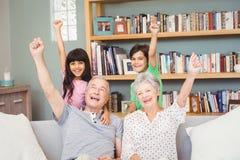 Grandchildren with grandparents gesturing success sign Stock Photo