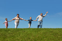 Grandchildren and grandparents running on hill Stock Image