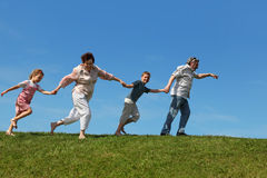 Grandchildren and grandparents running on lawn Royalty Free Stock Image