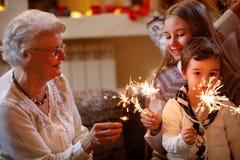 Grandchildren and grandparents with sprinklers celebrating xmas. Smiling grandchildren and grandparents with sprinklers celebrating xmas stock photography