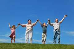 Grandchildren and grandparents standing on lawn. Grandchildren and their grandparents standing on lawn and holding for reared hands royalty free stock photos