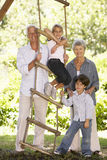 Grandchildren And Grandparents Standing By Tree House In Garden Royalty Free Stock Image