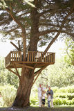 Grandchildren And Grandparents Standing By Tree House In Garden Stock Images