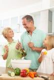 Grandchildren Helping Grandfather To Prepare Salad Stock Image