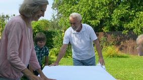 Grandchildren helping grandparents to set table with white cloth, holiday visit. Stock footage stock video footage