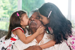 Grandchildren kissing grandparent. Portrait Indian family at home. Grandchildren kissing on grandparent face. Asian people living lifestyle royalty free stock image