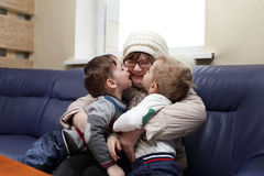 Grandchildren kissing their grandmother Stock Photography