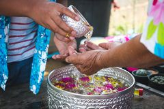 Grandchildren pour water on the hands of revered elders. Grandchildren pour water on the hands of revered elders and ask for blessing in the Songkran festival Royalty Free Stock Images