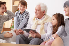 Grandchildren teaching grandpa to use a tablet royalty free stock photo