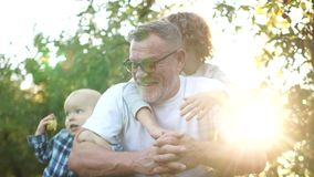 Grandchildren, toddler and teenage boy hug their happy grandfather standing in the apple orchard at sunset