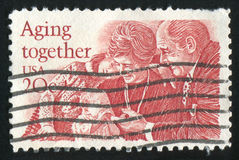 Grandchildren. UNITED STATES - CIRCA 1982: stamp printed by Umited States, shows Old Couple with Grandchildren, circa 1982 royalty free stock image