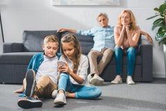 Grandchildren using smartphone. While grandparents sitting behind stock image