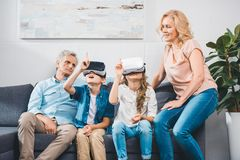 Grandchildren using virtual reality headsets stock photos