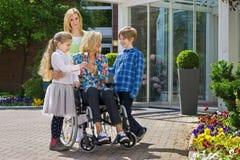 Grandchildren visiting grandmother in wheelchair Stock Images