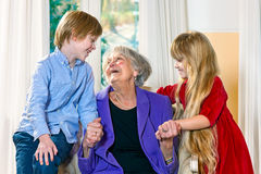 Grandchildren visiting their elderly grandmother. With a cute little boy and girl holding her hands and smiling happily at each other in a sign of love and stock photos