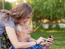 Grandmother and teenager girl Granddaughter. Grandchilds help the grandmother to master the smart phone stock image