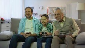 Granddad και μπαμπάς ενθαρρυντικοί για το αγόρι που παίζει την τηλεοπτική δραστηριότητα παιχνιδιών, χόμπι και ελεύθερου χρόνου φιλμ μικρού μήκους