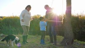 Granddad που κάνει την ταλάντευση στο δέντρο για τα μικρά παιχνίδια αγοριών και grandma με το εσωτερικό κατοικίδιο ζώο στη φύση σ απόθεμα βίντεο